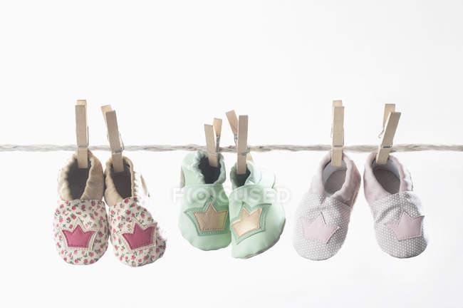 Sapatos de bebê pendurados na linha de roupas — Fotografia de Stock