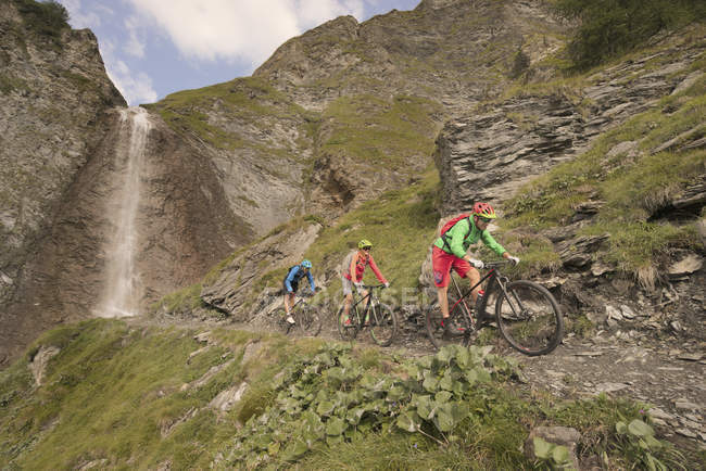 Mountainbiker fahren auf Hügel am Wasserfall — Stockfoto