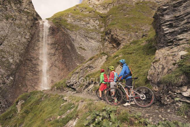 Mountain-Biker-Freunde beobachten Wasserfall — Stockfoto