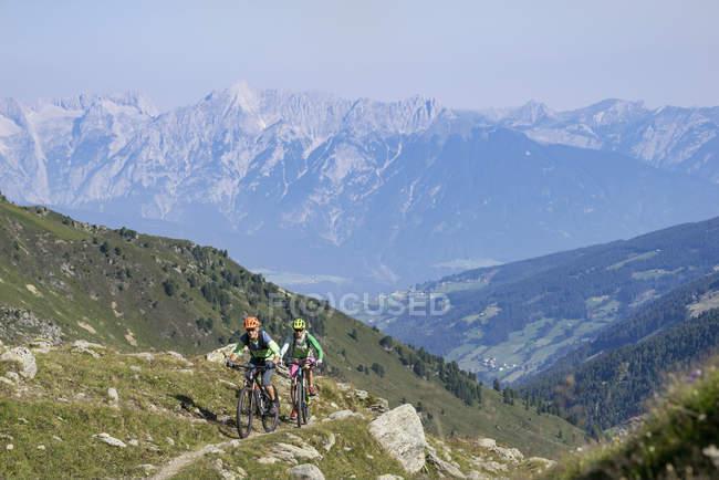 Друзья-велосипедисты едут в гору — стоковое фото