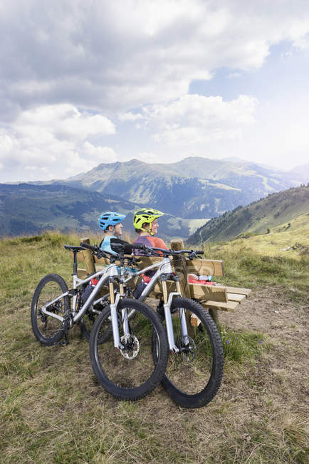 Mountain bikers sitting on bench in alpine landscape — Stock Photo