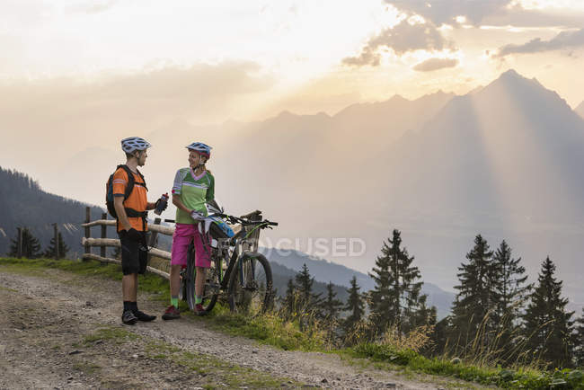 Горные велосипедисты, стоящие на грунтовой дороге — стоковое фото