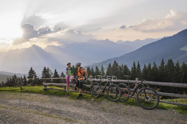 Mountain bikers standing by wooden fence — Stock Photo