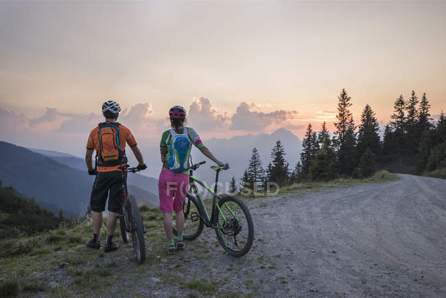Горные велосипедисты, стоящие на альпийском ландшафте — стоковое фото