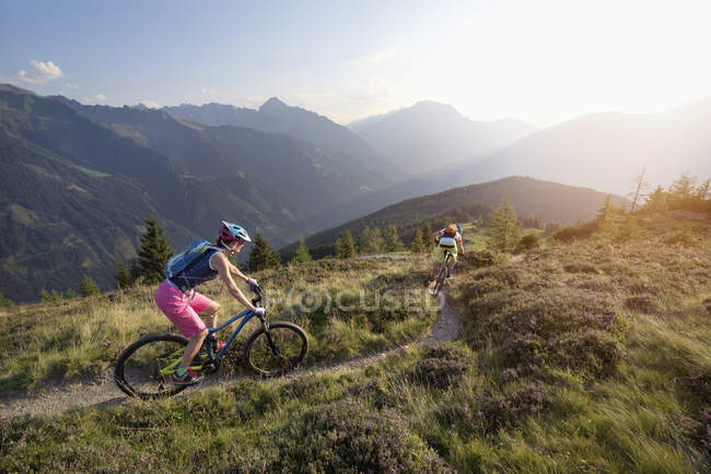 Mountain bikers riding on hill in alpine landscape — Stock Photo