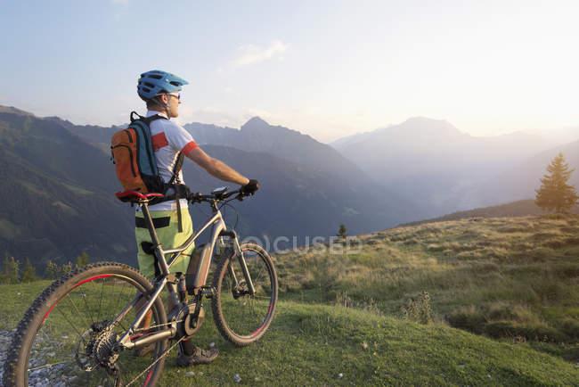 Горный велосипедист стоит на альпийском ландшафте — стоковое фото