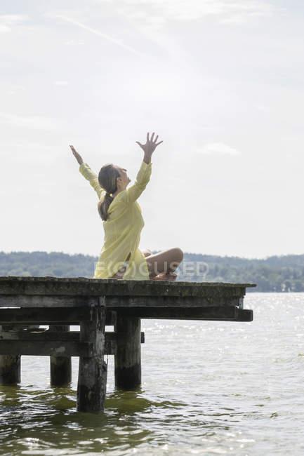 Frau mit erhobenen Armen sitzen auf Promenade — Stockfoto
