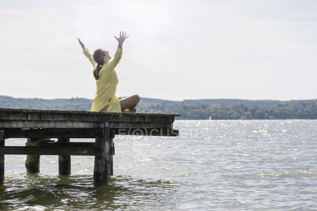 Femme avec les bras levés assis sur la promenade — Photo de stock