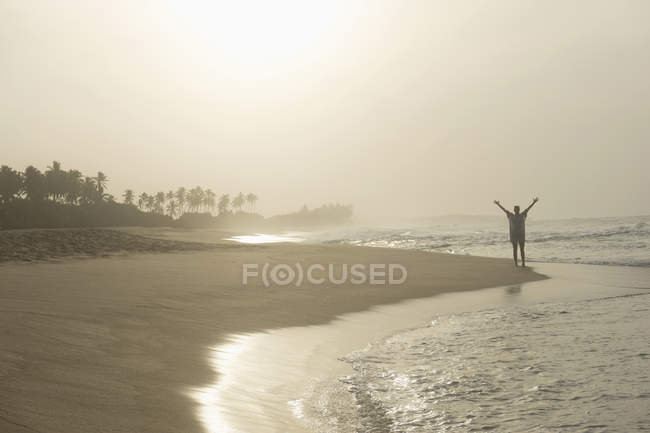 Woman standing with spreading hands on beach — Stock Photo