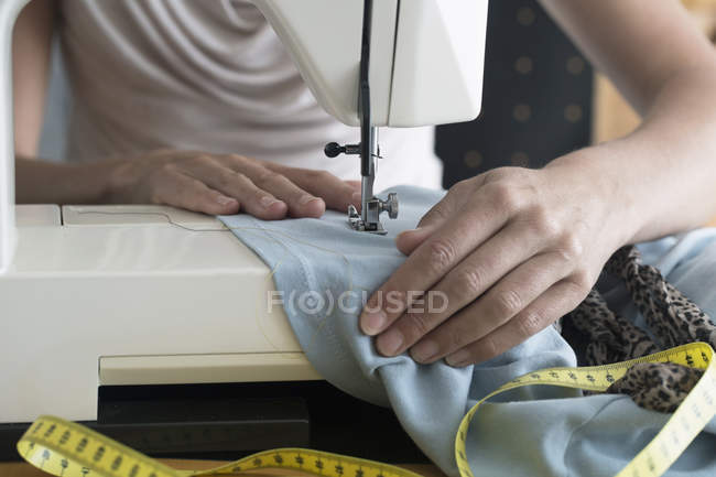 Dressmaker stitching cloth on sewing machine — Stock Photo