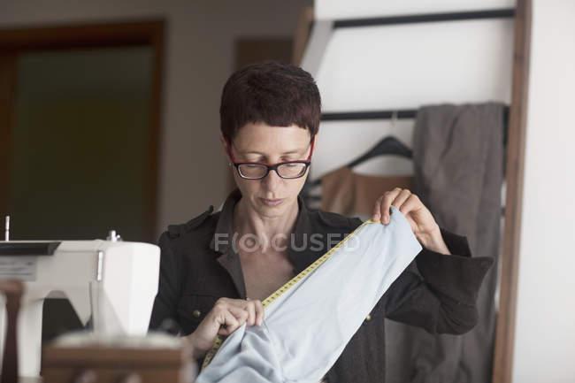 Female dressmaker measuring fabric — Stock Photo