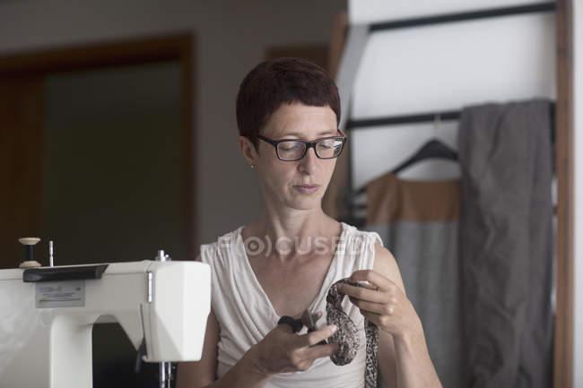Female dressmaker cutting fabric — Stock Photo