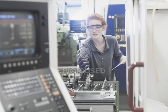 Engenheiro olhando para a parte da máquina — Fotografia de Stock