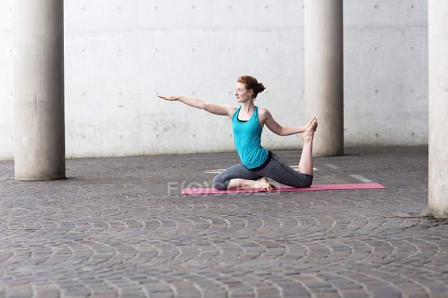 Женщина занимается йогой на коврике для упражнений — стоковое фото