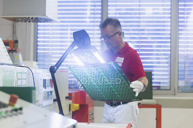 Ingénieur examinant carte de circuit imprimé — Photo de stock