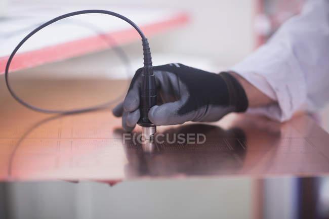 Menschliche Hand, die Platine zu prüfen — Stockfoto