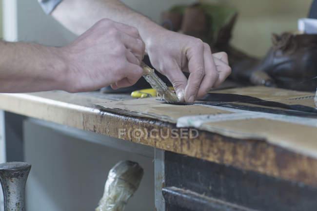 Sapateiro aplicando cola no sapato — Fotografia de Stock