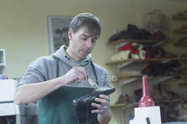 Sapateiro aplicando cola na sola — Fotografia de Stock
