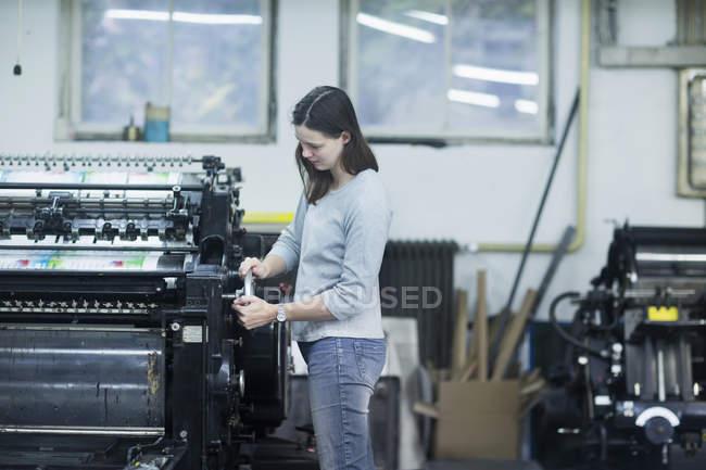 Imprimir trabalhador ajustando a máquina de impressão — Fotografia de Stock