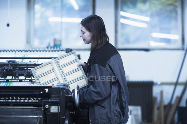 Print worker adjusting printing machine — Stock Photo