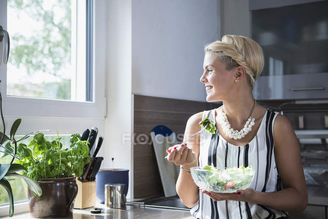 Женщина ест салат на кухне — стоковое фото