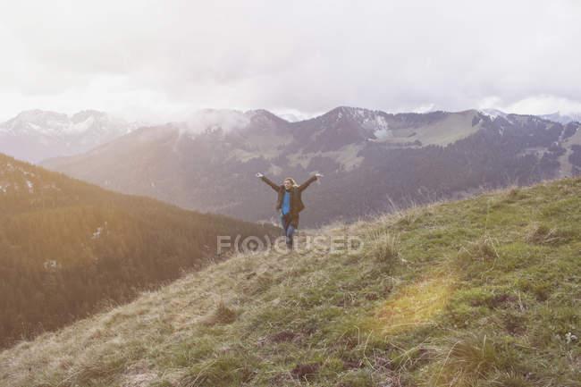 Mulher com os braços levantados em pé na montanha — Fotografia de Stock