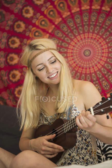 Woman playing ukulele in bedroom — Stock Photo