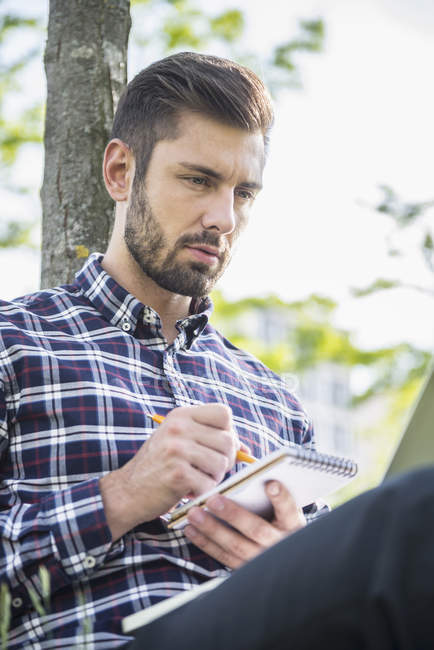 Man sitting in park and writing in notepad — Stock Photo