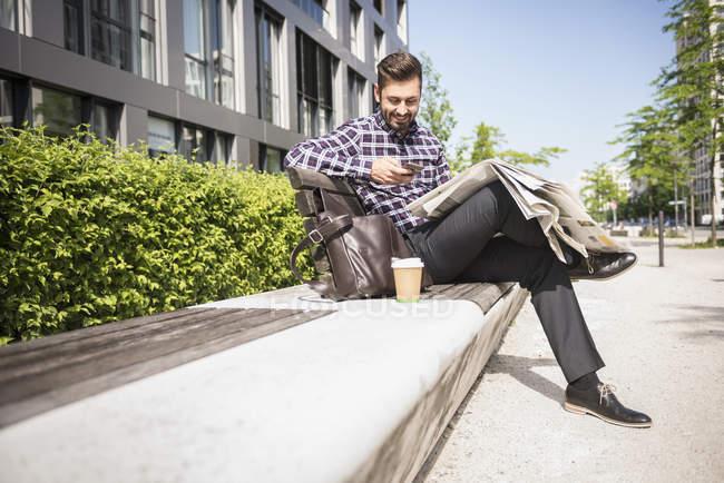 Человек сидит на скамейке и текстовых сообщений — стоковое фото