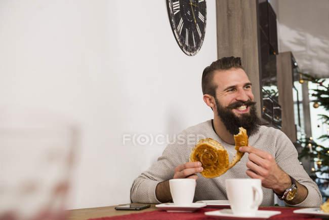 Man eating rolled bun — Stock Photo