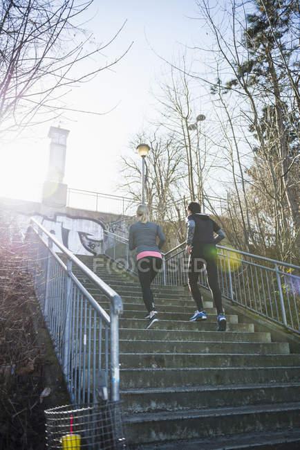Mann und Frau, die Treppe hinauf Joggen — Stockfoto