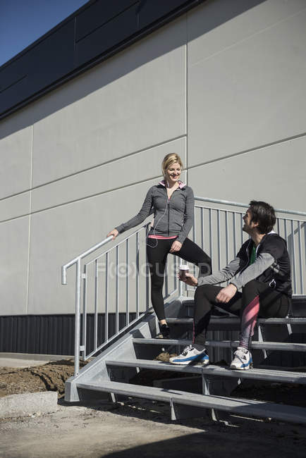 Man and woman relaxing on steps after workout — Stock Photo