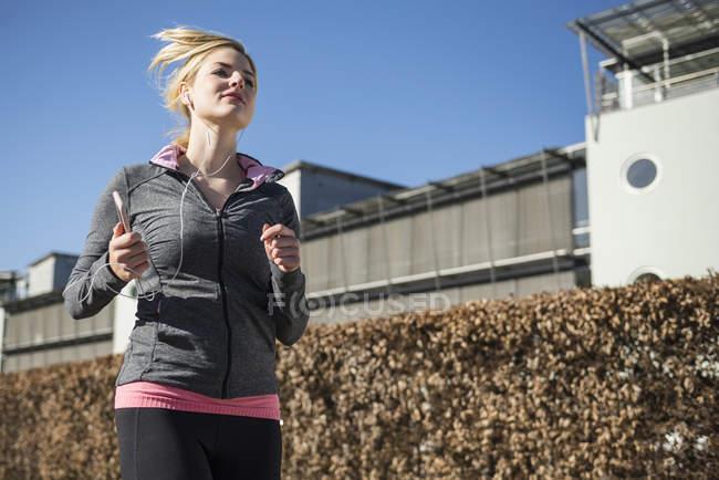 Женщина в спортивной одежде бегает трусцой и слушает музыку — стоковое фото