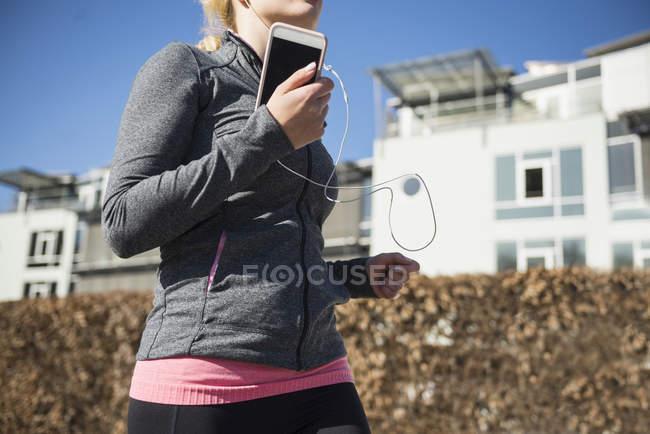 Женщина бегает и слушает музыку — стоковое фото