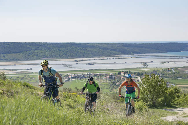 Motociclisti che salgono attraverso erba e case — Foto stock