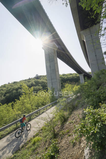 Байкер верхом велосипед на дороге ниже повышенных дорог — стоковое фото