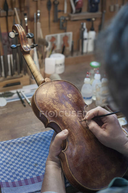 Violin maker painting violin — Stock Photo