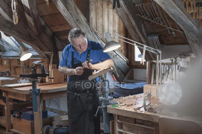Craftsman carving at workshop — Stock Photo
