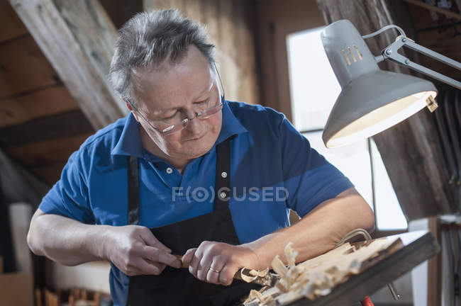 Craftsman carving violin — Stock Photo