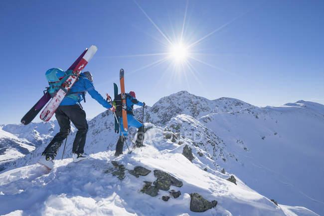 Лыжники, восхождение на хребте горы снега — стоковое фото