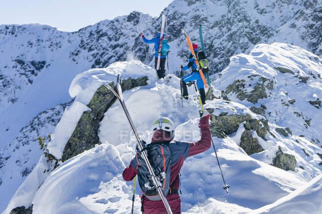 Лыжники, забравшись на снежные горы — стоковое фото