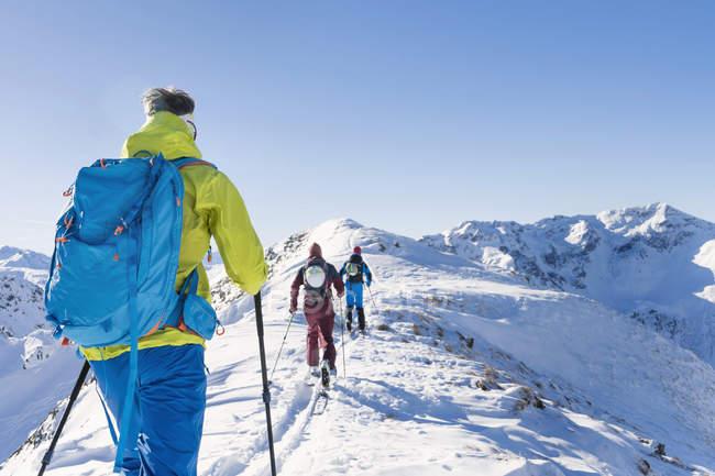 Лыжники, ходить на хребте горы — стоковое фото