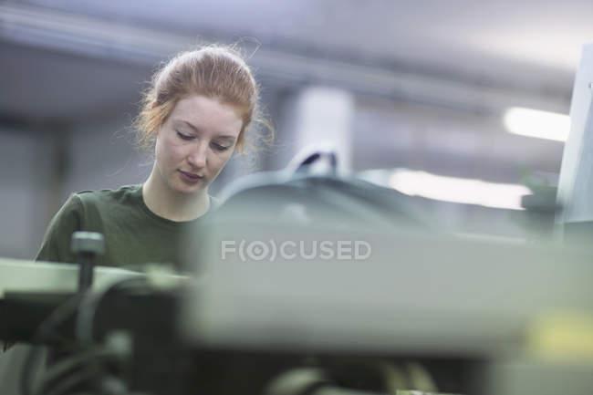 Mulher que trabalha pela máquina de prensa — Fotografia de Stock