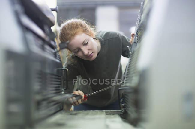 Print worker repairing print machine — Stock Photo