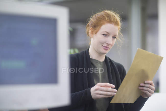 Confident print worker reading document — Stock Photo