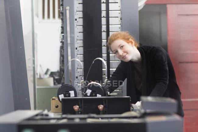 Woman standing by printing press machine — Stock Photo