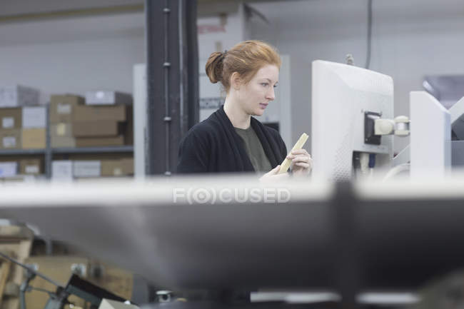 Print worker working by printing equipment — Stock Photo