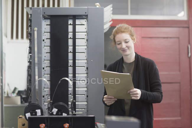 Mulher em pé pela máquina de prensa — Fotografia de Stock