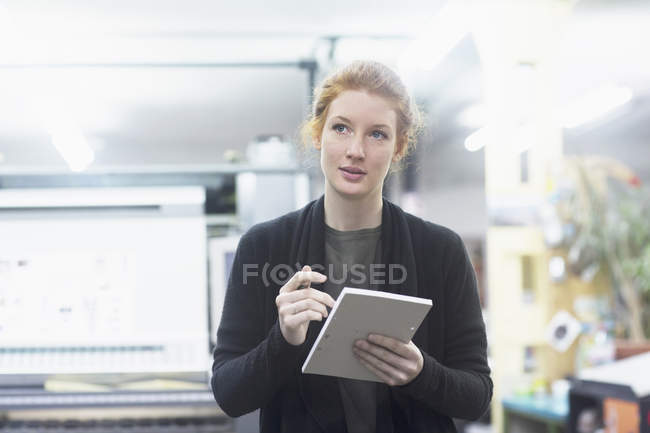 Contemplative female worker preparing list — Stock Photo