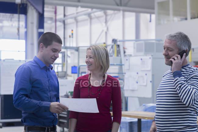 Empresario sosteniendo documento mientras lleva a la mujer de negocios - foto de stock